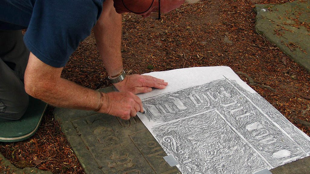 Volunteer Martin Broadbent carries out a gravestone rubbing as part of a project documenting the stones in St Mary's Old Churchyard.