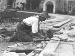 One of the estate workers laying the paving stones in the courtyard to Farrand's design Photo: George Bennett, ©The Dartington Hall Trust Archive