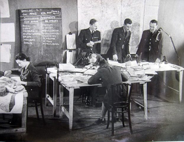 Bill Hunter (standing at the table, centre) in the RAF's Central Information Unit office, July 1942. (c) Andrew Hunter